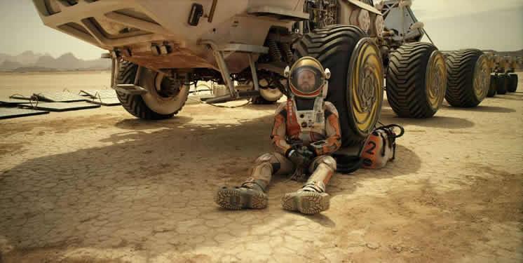 "Matt Damon (""Mark Watney"") se apoya en un rover."