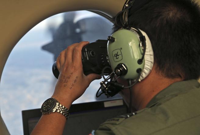 Un miembro de los equipos de búsqueda observa el mar desde un avión.
