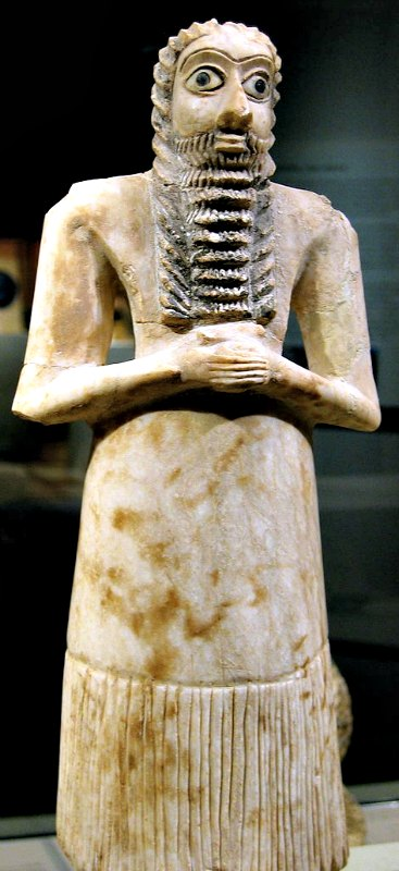 """Figura votiva de un hombre en actitud de veneración, del 2700 a. C. – 2600 a. C., época en la que Enlil era considerado el dios principal. Hallada en las ruinas del """"templo cuadrado"""" de Eshnunna (actual Tell Asmar); alabastro, caracolas, caliza negra y betún. Museo Metropolitano de Arte de Nueva York, Estados Unidos."""