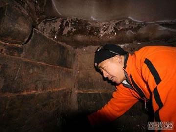 Miembro del equipo de investigadores descubre una antigua construcción de madera.