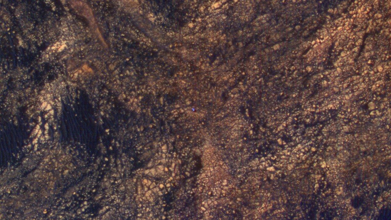 El punto azul que aparece en el centro de la fotografía es el rover Curiosity mientras escala el Monte Sharp en Marte.