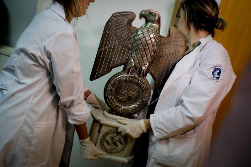 Miembros de la Policía Federal de Argentina trasladan la estatua de un águila.