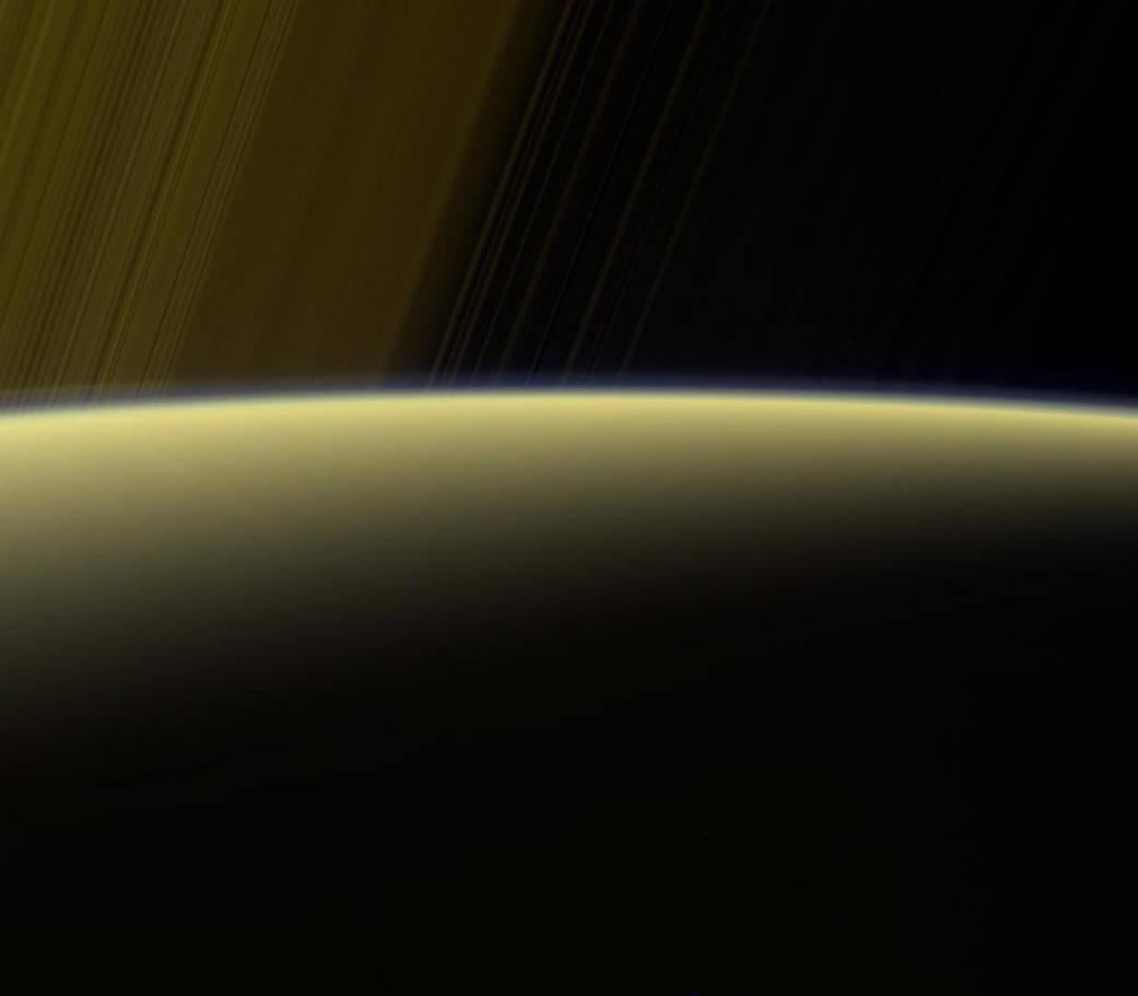 Esta visión de color falso de la nave Cassini de la NASA muestra los anillos más allá del horizonte iluminado por el sol de Saturno. A lo largo de la extremidad (el borde del planeta) en la izquierda se puede ver una niebla fina, separada. Esta neblina desaparece hacia el lado derecho de la escena.