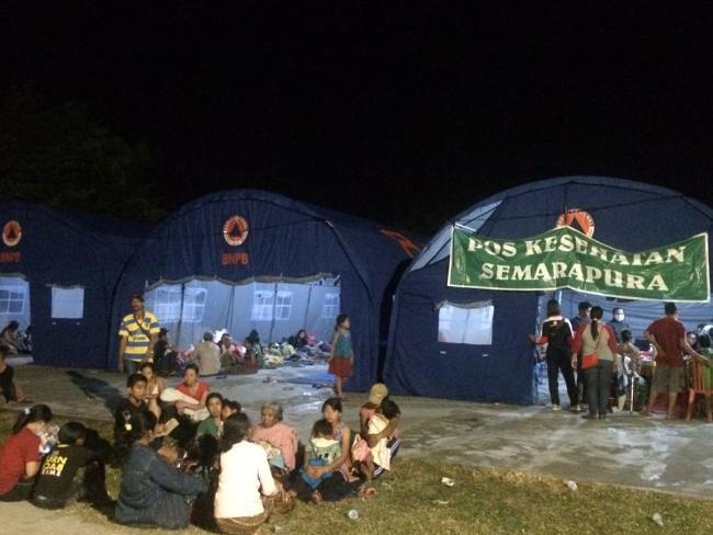 Los aldeanos que fueron evacuados de sus hogares en la ladera del monte Agung se sientan fuera de las tiendas preparadas para convertirse en su refugio temporal en Klungkung, Bali, Indonesia.