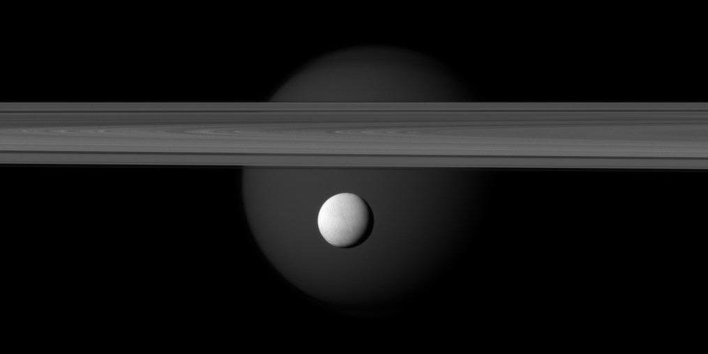 Encelado (primer plano) se desplaza frente a los anillos de Saturno mientras Titán se asoma detrás