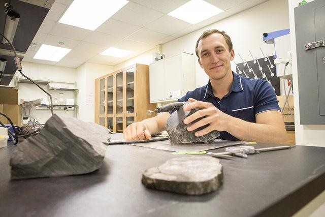 Erik Gulbranson, paleoecólogo y profesor asistente visitante en UWM, estudia algunos de los árboles fosilizados que trajo de la Antártida. Gulbranson regresará allí para realizar más investigaciones este año