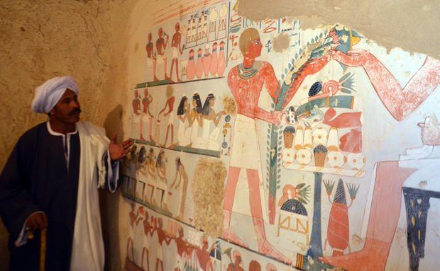 Un trabajador egipcio se encuentra junto a un antiguo mural egipcio