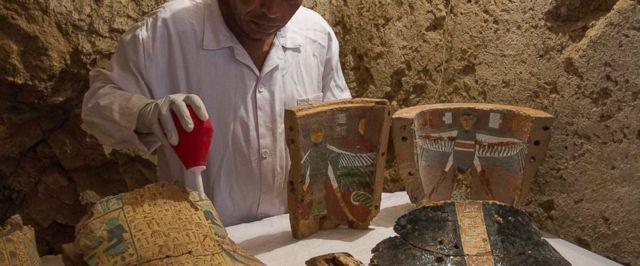 Un trabajador de excavación egipcio restaura muebles funerarios hallados recientemente
