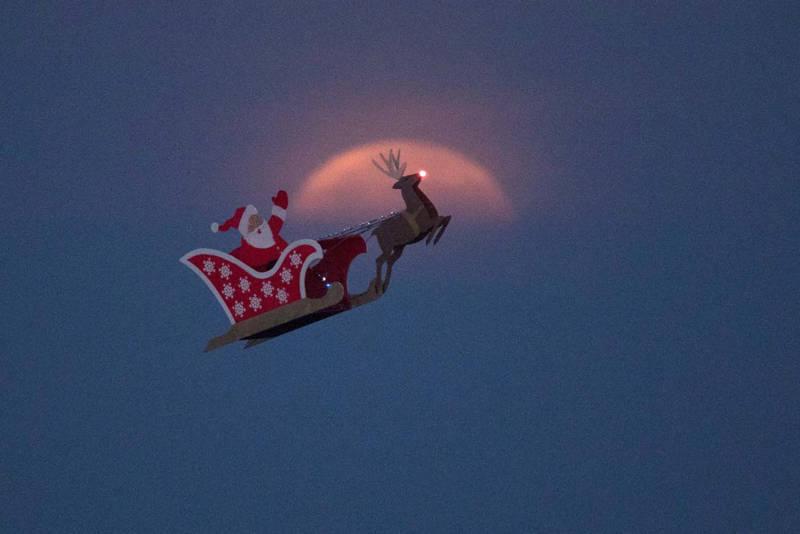 Un Santa a control remoto hace su vuelo de prueba acompañado con el fondo de la superluna