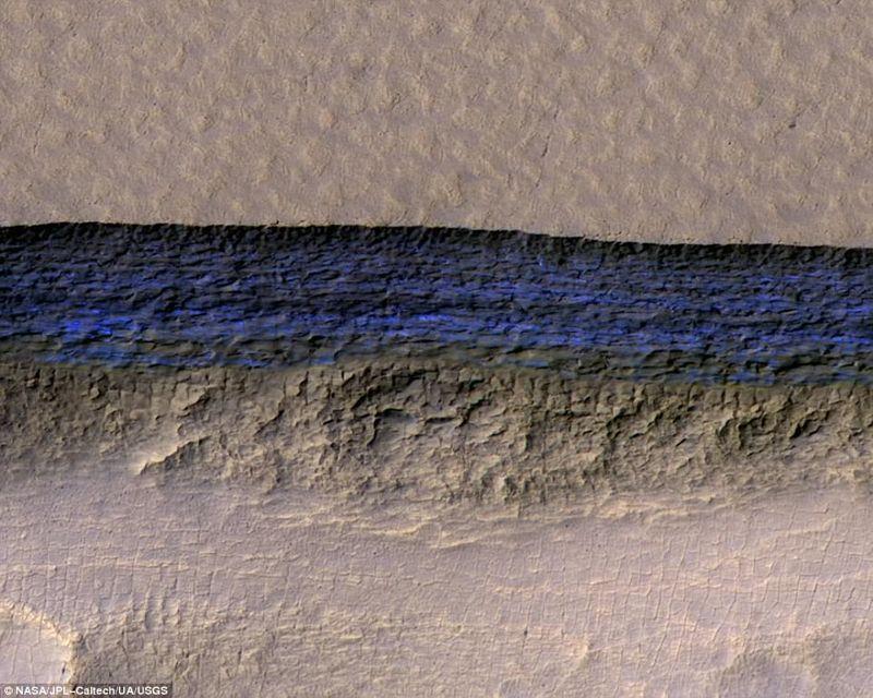 Una sección transversal de hielo subterráneo se expone en la pendiente pronunciada que aparece de color azul brillante en esta vista de color mejorado de la cámara HiRISE en el Mars Reconnaissance Orbiter de la NASA