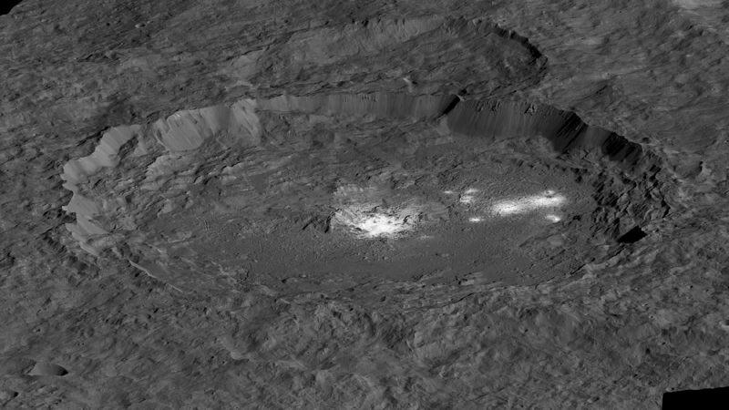 Misteriosos puntos brillantes que salpican la superficie del planeta enano Ceres han desconcertado a los científicos desde que fueron descubiertos por primera vez hace dos años. La nave espacial Dawn de la NASA capturó las primeras imágenes de dos áreas claramente reflectantes en 2015