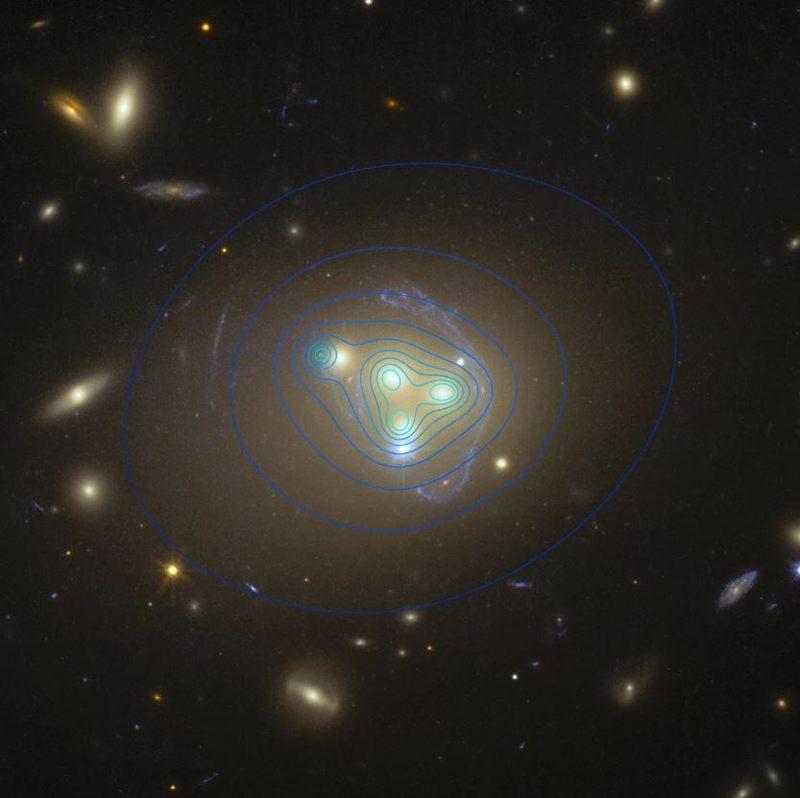La distribución de la materia oscura en el cúmulo de galaxias Abell 3827 aparece como líneas de contorno azules en esta foto del Telescopio Espacial Hubble