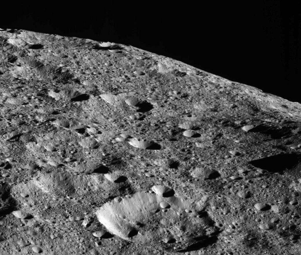 Dawn capturó esta vista el 16 de mayo de 2018 desde una altitud de aproximadamente 440 kilómetros. El cráter grande cerca del horizonte tiene aproximadamente 35 kilómetros de diámetro. El cráter mediano en el primer plano se encuentra a unos 120 kilómetros del gran cráter.