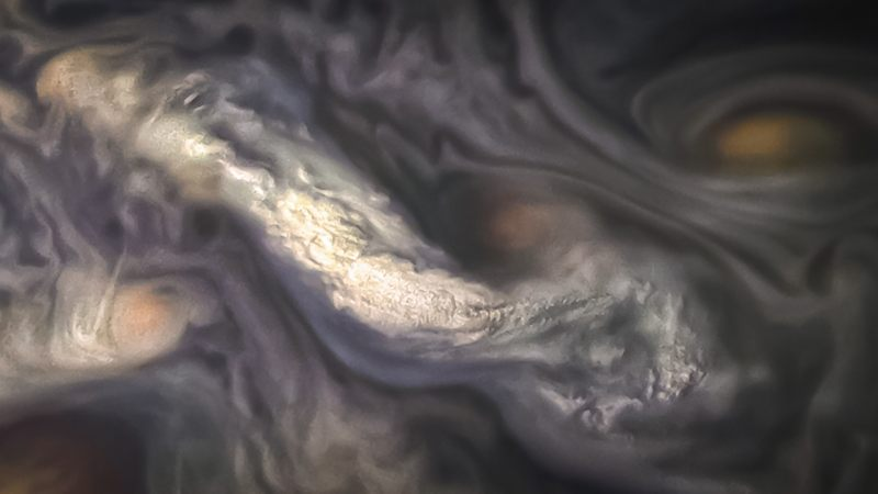 Esta imagen captura una formación de nubes a gran altitud rodeada por patrones de remolinos en la atmósfera de la región del Cinturón Templado Norte Norte de Júpiter