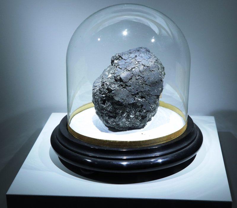 Este es el meteorito carbonático Orgueil, un tesoro científico que cayó en 1864 en el suroeste de Francia. La masa principal del meteorito se puede ver en la exposición de meteoritos en el Museo Nacional de Historia Natural de París hasta enero de 2019. El soporte sobre el que se muestra el meteorito mide aproximadamente 30 cm de ancho
