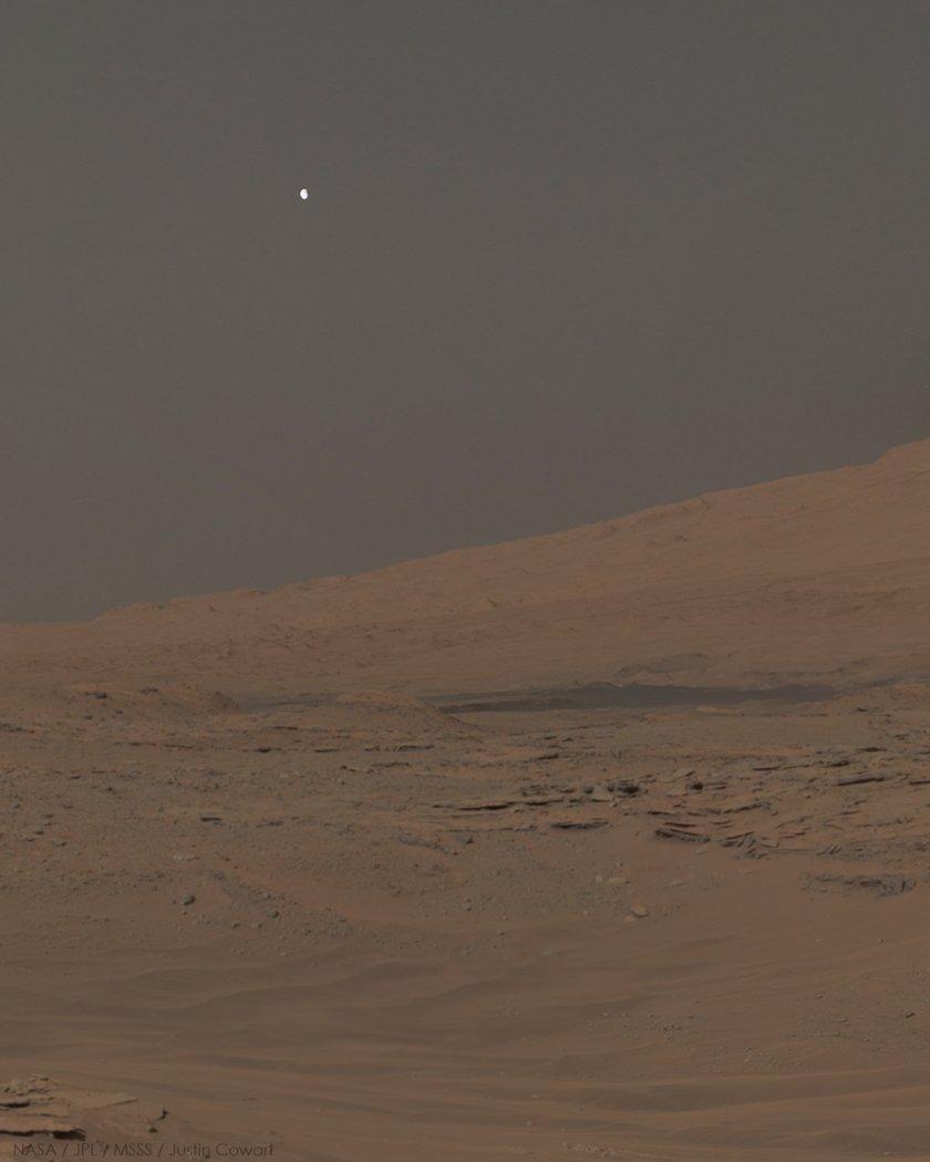 Phobos visto sobre el Monte Sharp, Marte, en un mosaico de tres imágenes capturadas por el rover Curiosity en 2014
