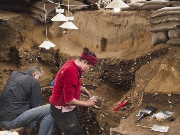 Un grupo de arqueólogos trabajan dentro de la cueva de Blombos