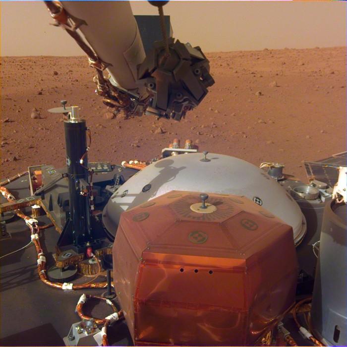 Esta imagen de la cámara montada en el brazo robótico de InSight muestra los instrumentos en la cubierta de la nave espacial, con la superficie marciana de Elysium Planitia en el fondo