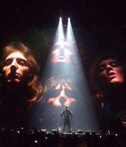 Imagen proyectada de los integrantes de Queen durante una interpretación de Robbie Williams en 2015