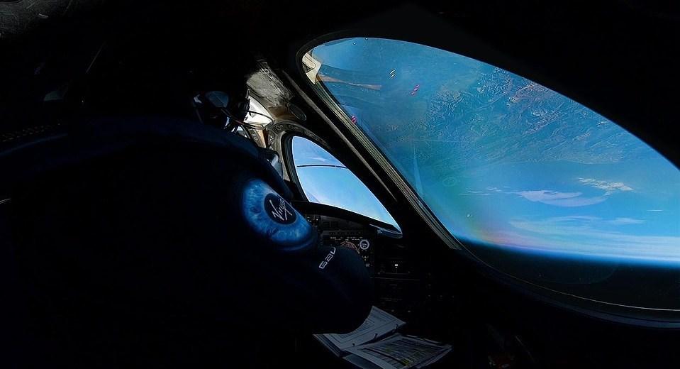 Uno de los pilotos mira a la Tierra desde la ventana de la nave VSS Unity