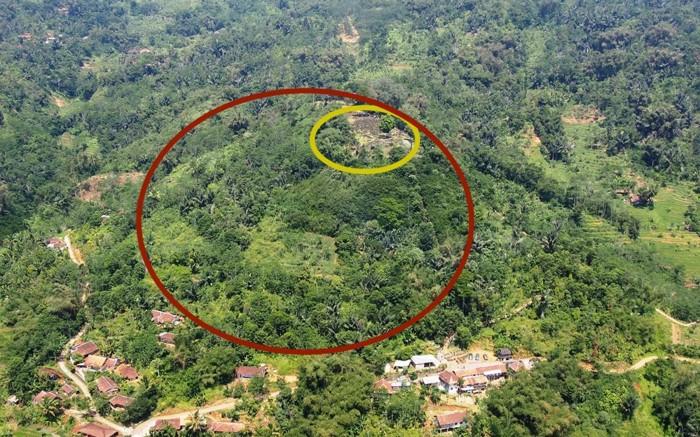 La estructura en forma de pirámide permaneció oculta durante mucho tiempo porque fue tapada por el follaje y, por lo tanto, parece una colina (círculo rojo), con un megalito expuesto en la parte superior (círculo amarillo)
