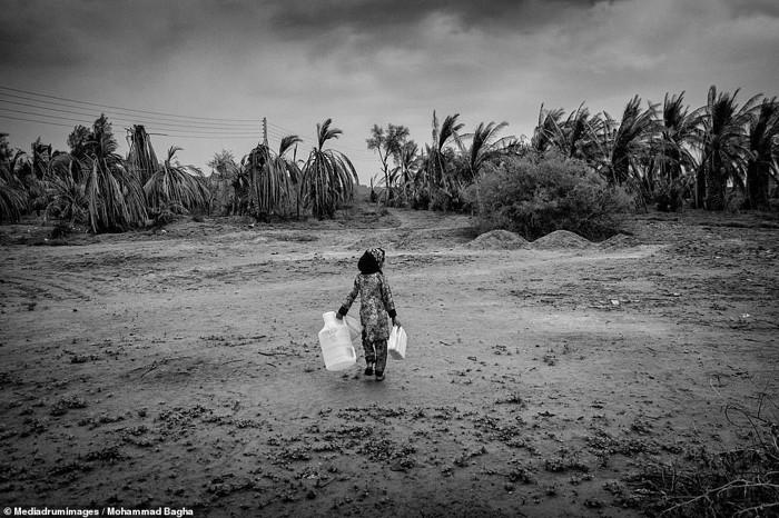 Una niña pequeña lleva barriles vacíos al pozo para llenarlos de agua, y que se encuentra a más de dos kilómetros de distancia de donde vive