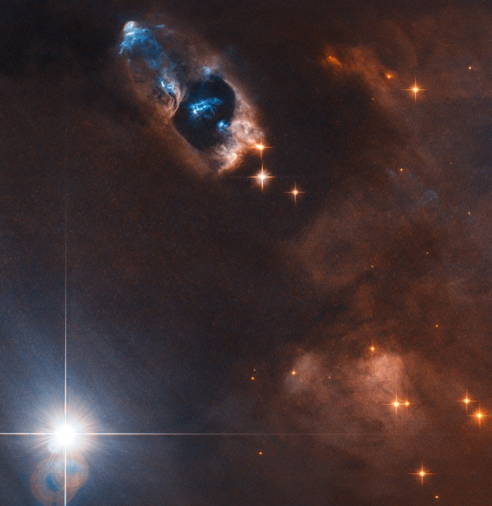 En esta imagen, el Telescopio Espacial Hubble de la NASA / ESA ha capturado la «pistola humeante» de una estrella recién nacida, los objetos Herbig-Haro numerados del 7 al 11 (HH 7–11). Estos cinco objetos, visibles en azul en la parte superior central de la imagen, se encuentran dentro de NGC 1333, una nebulosa de reflexión llena de gas y polvo que se encuentra a unos mil años luz de la Tierra