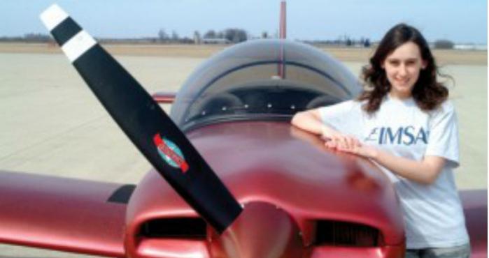 Sabrina Gonzalez Pasterski posando con el avión que ella misma construyó