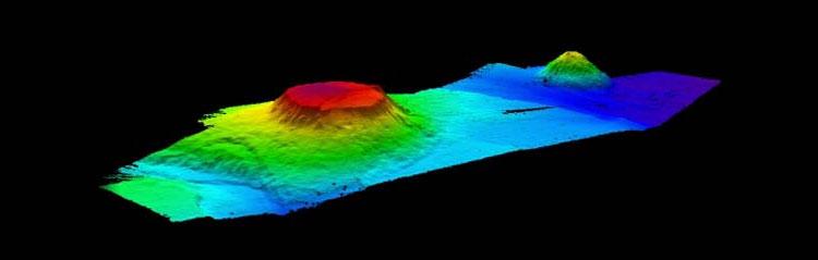 Los montes submarinos de Nueva Inglaterra conforman la cadena de montes submarinos más larga en el Atlántico Norte, formando una cadena de picos submarinos con tendencia al sureste que se extiende desde Bear Seamount por otras 1.126 km hasta Nashville Seamount. Esta imagen muestra Bear Seamount con Physalia Seamount en el fondo. A unas 321 km de Woods Hole, MA, el monte submarino de altura plana se eleva aproximadamente 2.000 metros desde el fondo del océano circundante hasta una profundidad de 1.100 metros