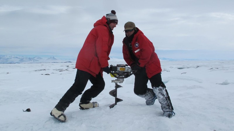 Los investigadores Grant Macdonald y Phillip Chung colocan un sismómetro en la plataforma de hielo McMurdo