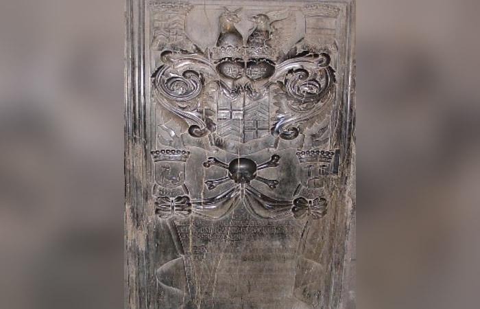 El Ave Fénix arriba y la calavera y los huesos cruzados en el centro. Grabado en iglesia católica