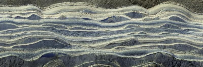 Esta imagen compuesta muestra capas alternas de hielo y arena en un área donde están expuestas en la superficie de Marte. El hielo de agua aparece como de color claro, mientras que la arena es azul oscuro