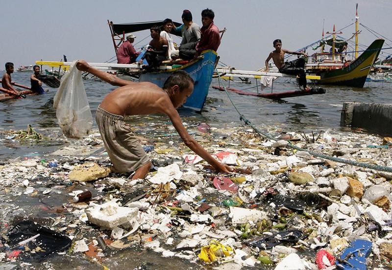 Un joven recoge plásticos en la costa de Manila, Filipinas, el 9 de abril de 2008
