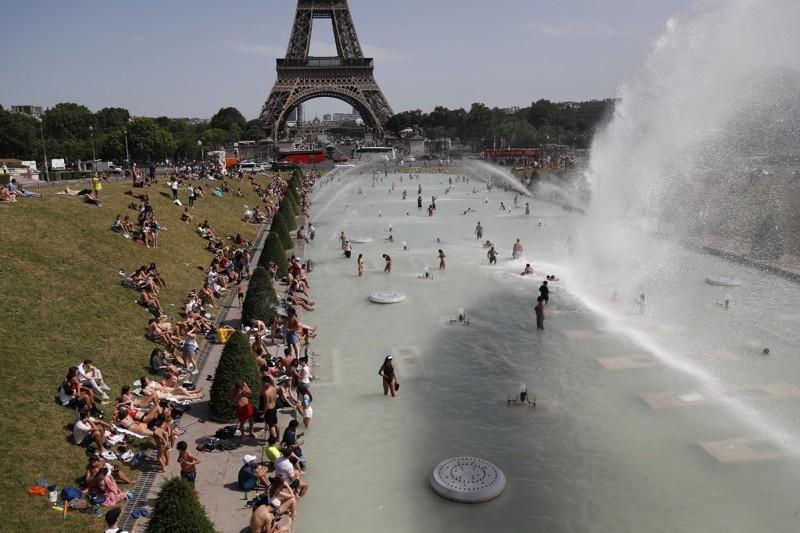 Gente refrescándose en la fuente del Trocadero, cerca de la Torre Eiffel en París