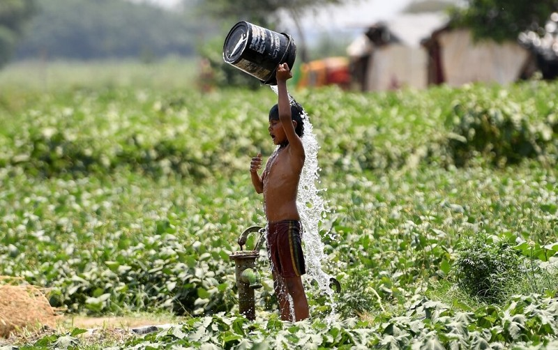 Un niño indio trata de refrescarse con agua en Nueva Delhi el 29 de mayo de 2019 durante una ola de calor