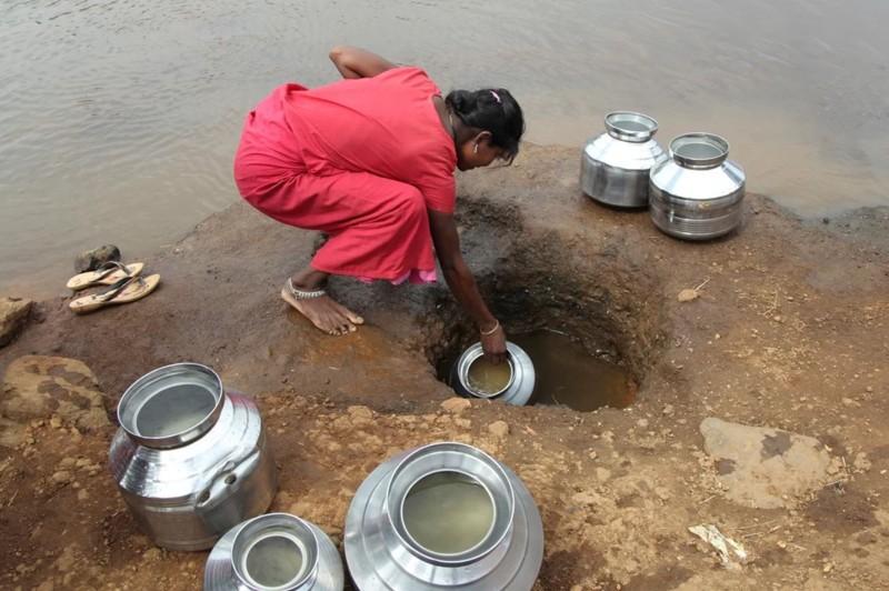 Una mujer saca agua de una abertura hecha para filtrar el agua junto a un lago contaminado en Thane, India