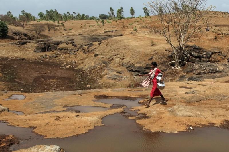Una mujer lleva jarras para sacar agua de una abertura hecha para filtrar el agua junto a un lago contaminado en Thane, India