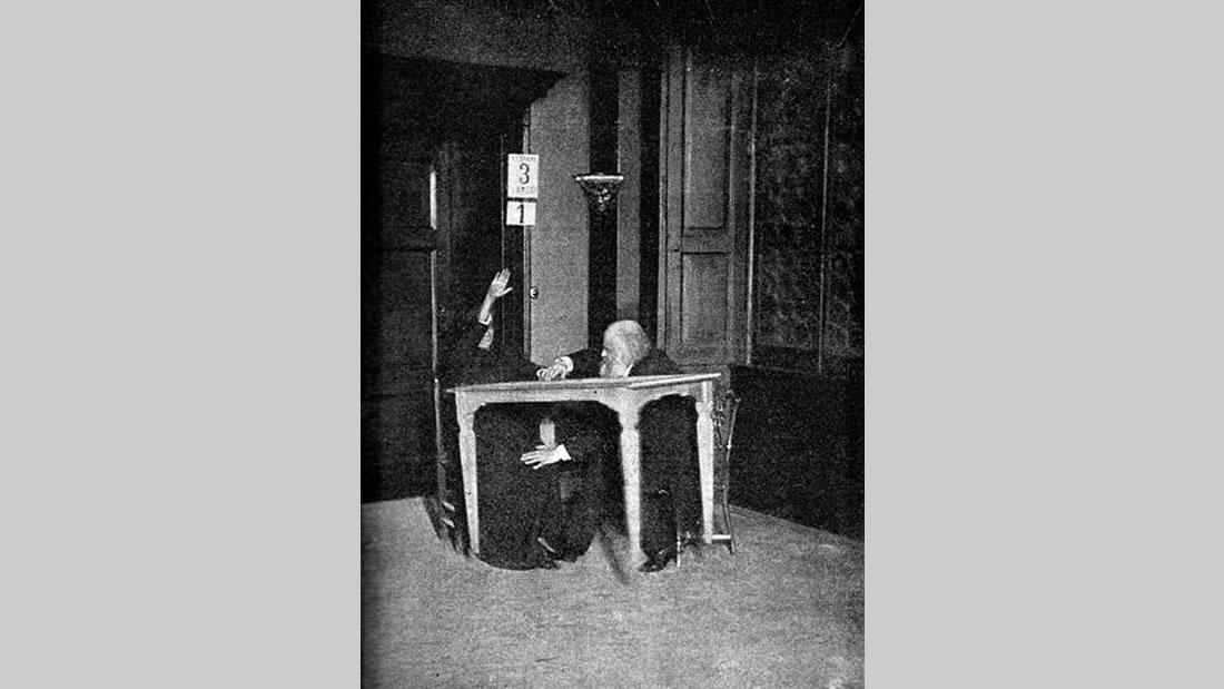 Eusapia Palladino hace levitar una mesa mientras es controlada por Alexandr Aksakov, Milán. (1892)