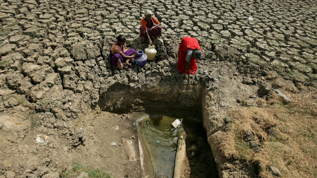 Las mujeres sacan agua de una abertura hecha por residentes en un lago seco en Chennai, India