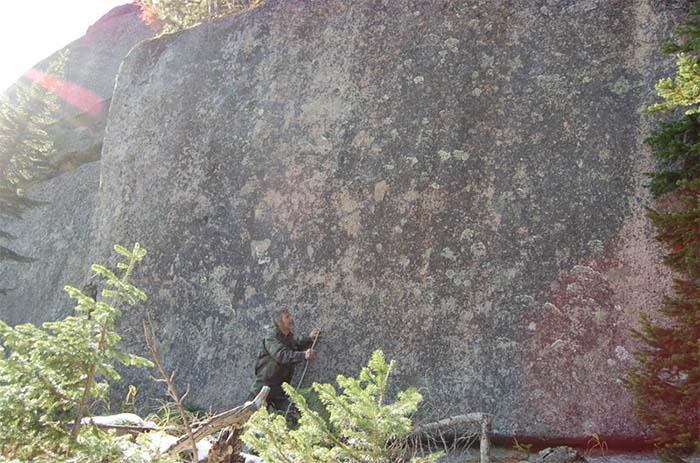 Explorador al lado de uno de los grandes bloques de granito