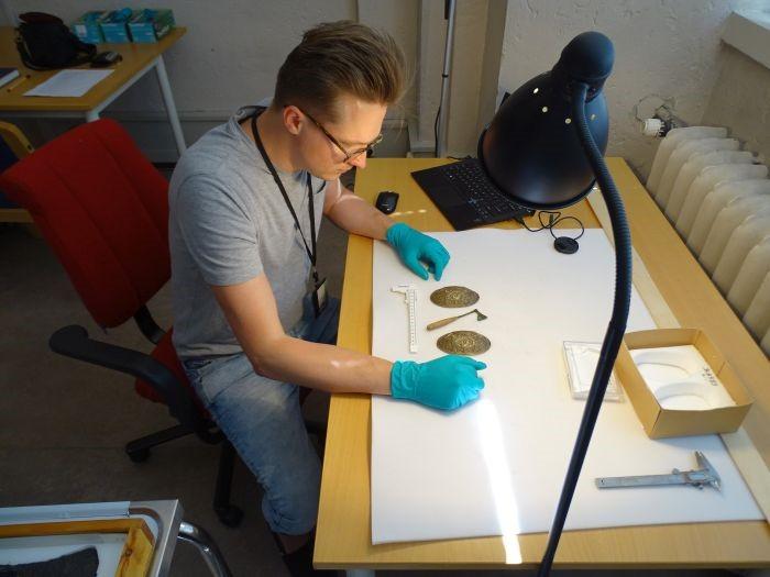 El Dr. Leszek Gardeła estudia un hacha en miniatura y joyas de una tumba de mujeres en Svingesaeter, Noruega