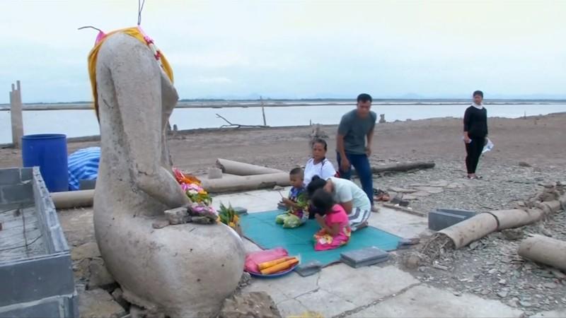 Visitantes adorando una estatua de Buda sin cabeza