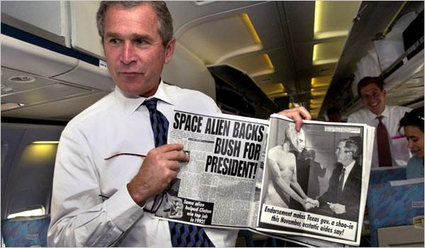 George Bush jr posa divertido, con un artículo que lo vincula al secreto ovni, y que su padre defendiera de cualquiera indiscreción. Fotograma del 2000, tan sólo un año después sucedería el enigmático atentando de las Torres Gemelas