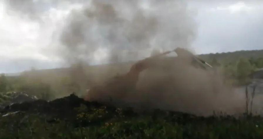 Un cargador intenta cubrir una mina a cielo abierto humeante con arcilla en Kiselyovsk la semana pasada