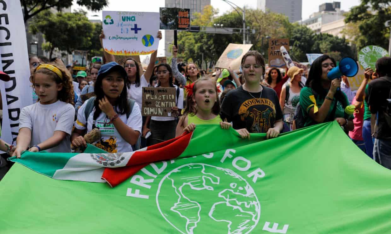 Niñas sostienen una bandera mientras participan en una manifestación de la huelga climática global en la Ciudad de México