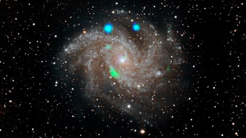 Esta imagen de luz visible de la galaxia Fireworks (NGC 6946) proviene del Digital Sky Survey, y se superpone con datos del observatorio NuSTAR de la NASA (en azul y verde)