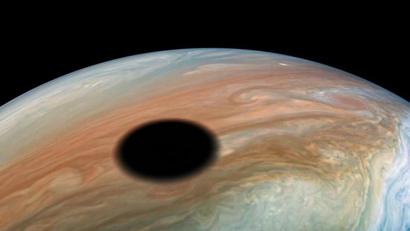 Una imagen increíble muestra la espeluznante sombra negra proyectada en la superficie giratoria de Júpiter por su luna Io cuando esta pasa entre el gigante gaseoso y el Sol
