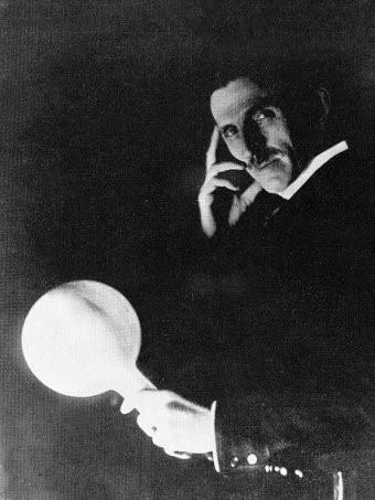 Nikola Tesla retratado en 1898, sosteniendo en sus manos, una de sus clásicas bombillas