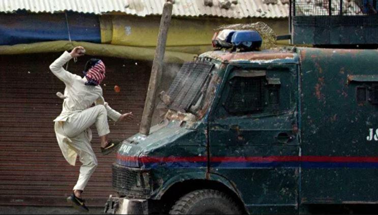 Un manifestante en Cachemira salta sobre un coche de policía indio