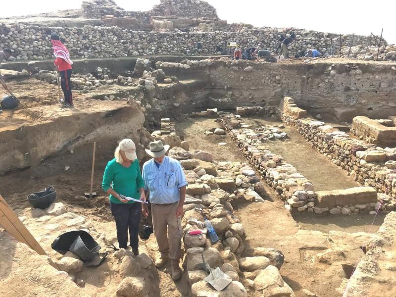 Investigadores cerca de las ruinas, con la capa de destrucción a la mitad de cada pared expuesta